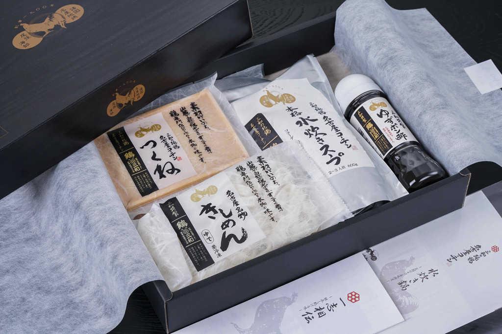 化粧箱の中で不織布に包まれた三和の純鶏名古屋コーチン水炊き鍋セットの具材