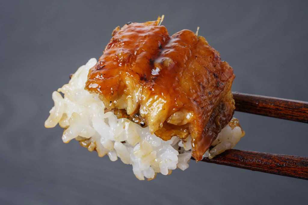 ひと口大のご飯とうなぎ蒲焼を箸で持ち上げる、鰻の蒲焼とご飯