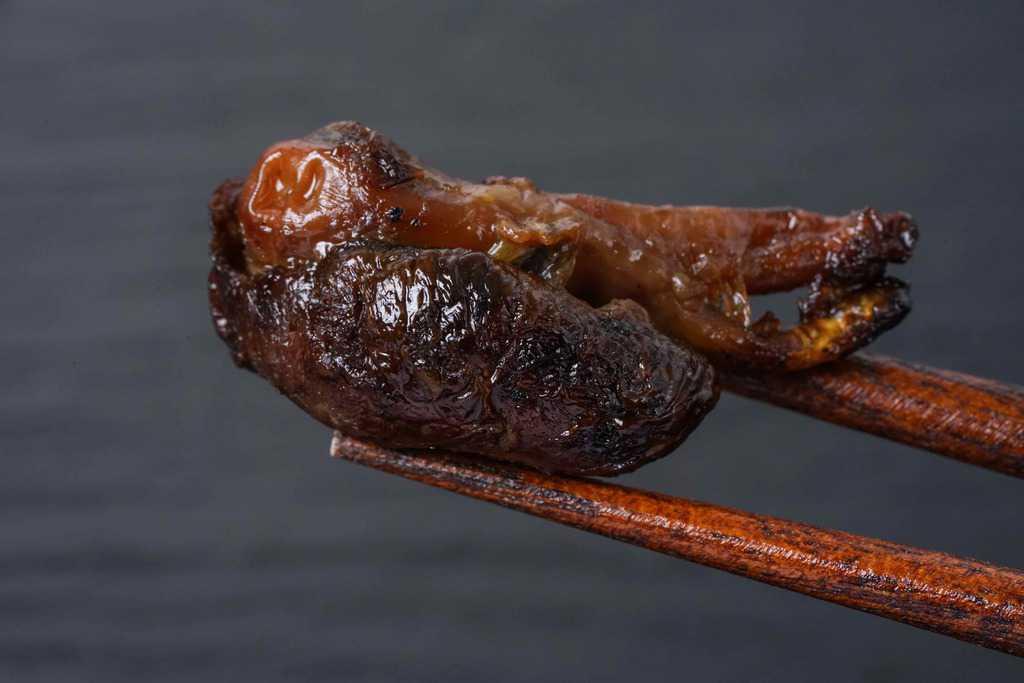 鰻の肝焼きを箸で持つ、箸でつまんだウナギの肝焼き