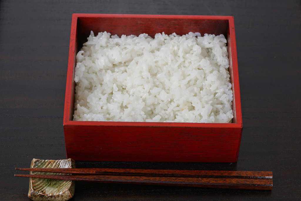 うな重箱に敷き詰めた炊きたてのご飯、重箱に入ったご飯と箸