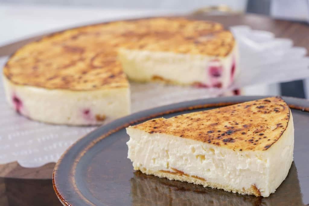 皿に盛り付けた御献上チーズケーキ1ピースを手前、奥にホールの御献上チーズケーキ
