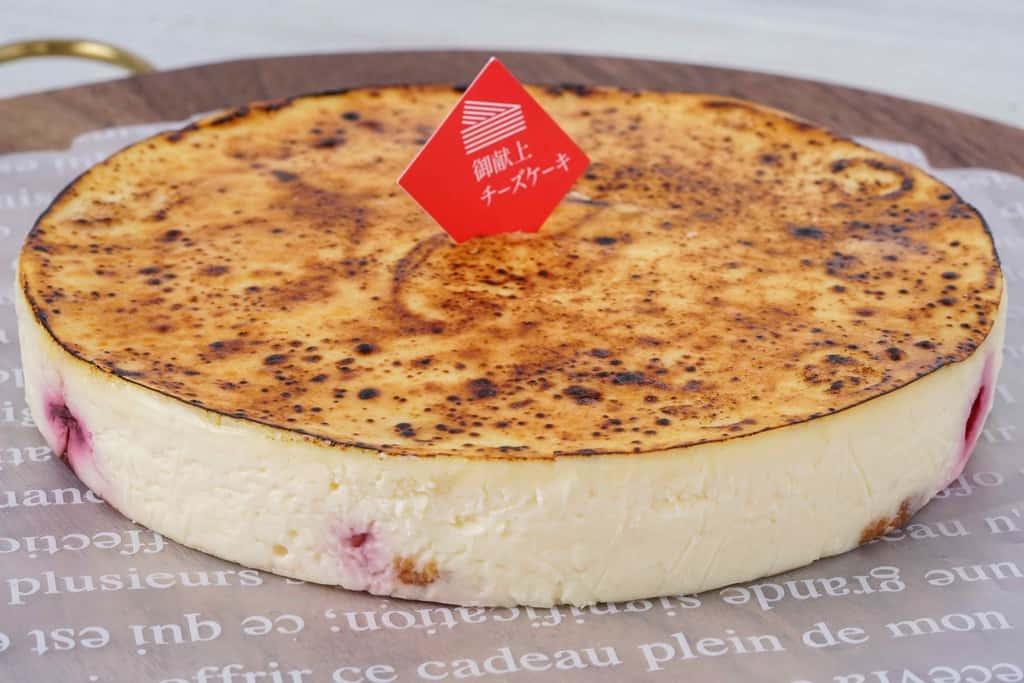 カッティングボードの上に乗った御献上カスティーラの御献上チーズケーキ、ホールサイズのチーズケーキ
