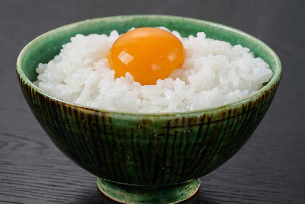 炊きたてご飯の上に田子たまご村のにんにく卵の黄身を乗せる、卵かけご飯