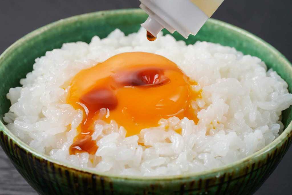炊きたてご飯の上に乗った生卵にたまごかけご飯のたれをかける