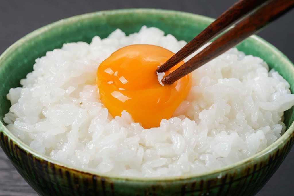 炊きたてご飯の上に乗った生卵の黄身を箸でつつく