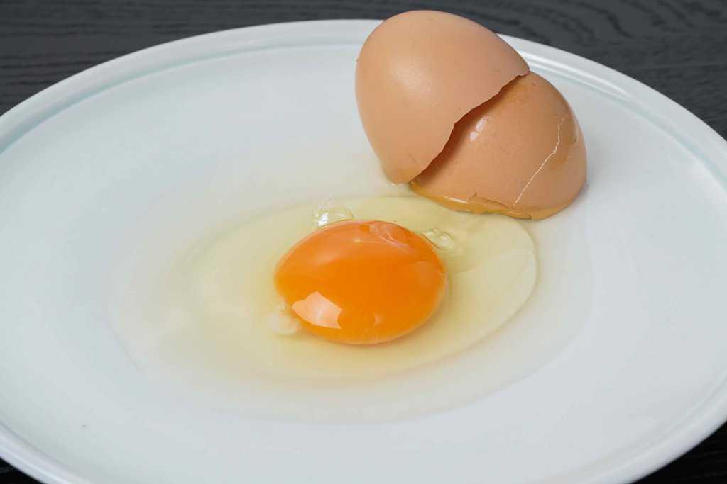 皿の上で割った田子たまご村のにんにく卵1個