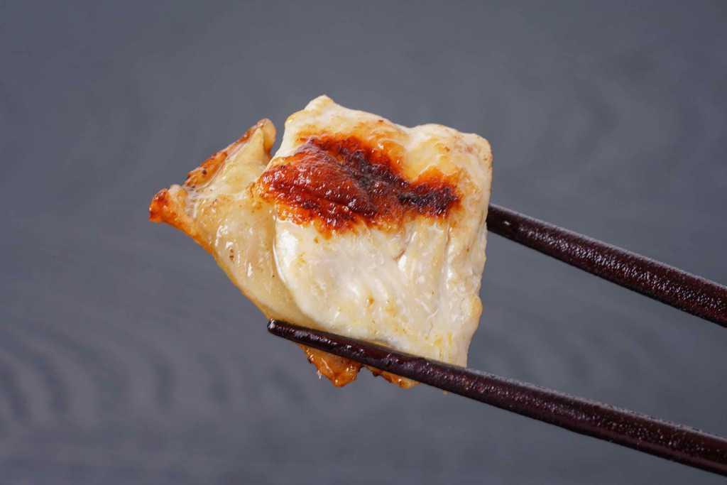 名古屋コーチンのムネ肉のグリルを箸でつまむ