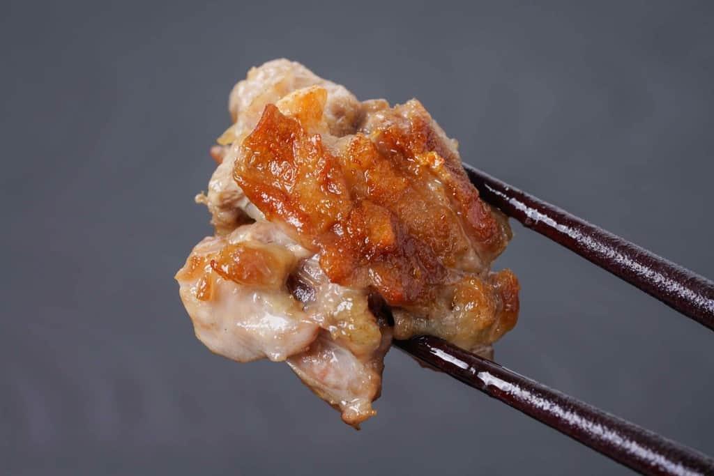 名古屋コーチンのせせり(首肉)のグリルを箸でつまむ
