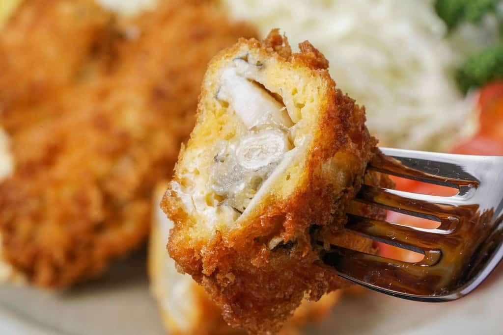 カキフライを半分に割ってフォークで持ち上げる、牡蠣フライの断面