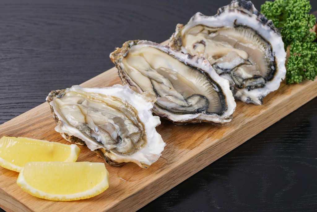 細長いカッティングボードの上のカットレモン2切れと殻をはずした生の牡蠣「カキえもん」3個とパセリ、生ガキ