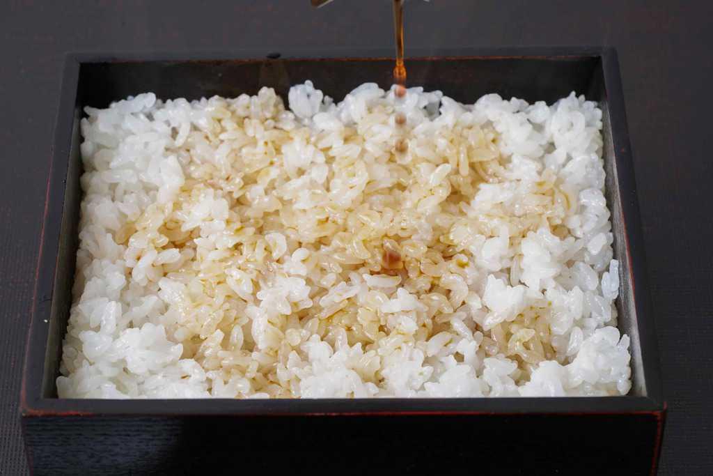 うな重箱の中のご飯にうなぎ蒲焼のたれをかける