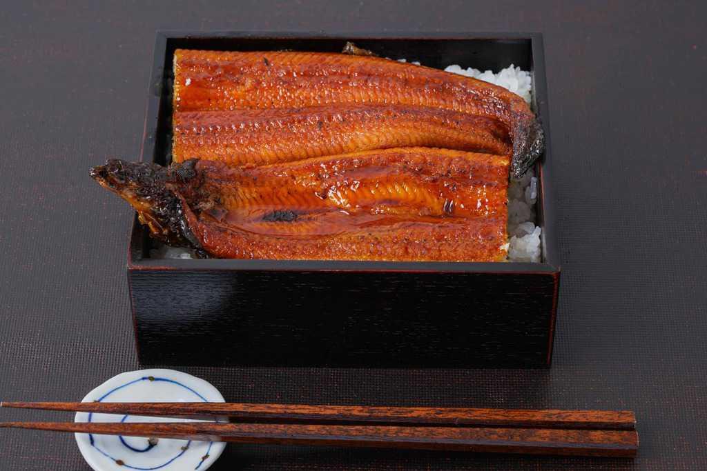 重箱に詰めたご飯の上に越前かに職人甲羅組の鹿児島県産特大うなぎ蒲焼きを半分にカットして盛り付け
