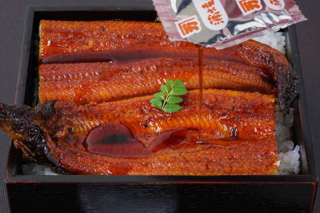 うな重に蒲焼のタレをかける、越前かに職人甲羅組の鹿児島県産特大うなぎ蒲焼きにたれをかける