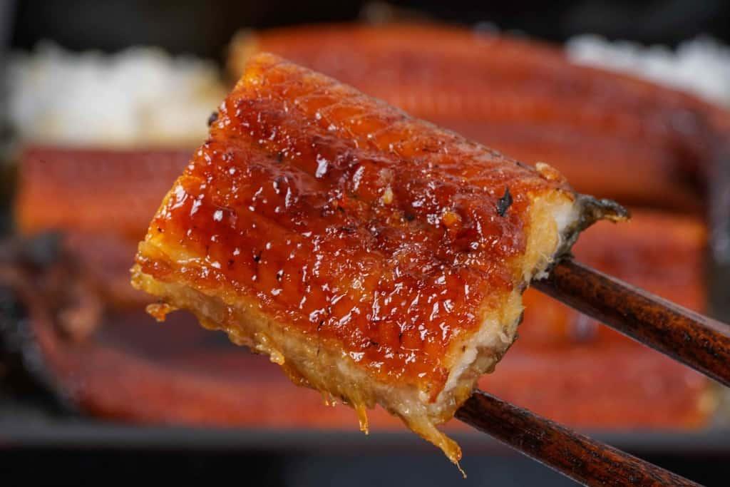 越前かに職人甲羅組の鹿児島県産特大うなぎ蒲焼きのひと切れを箸でつまむ