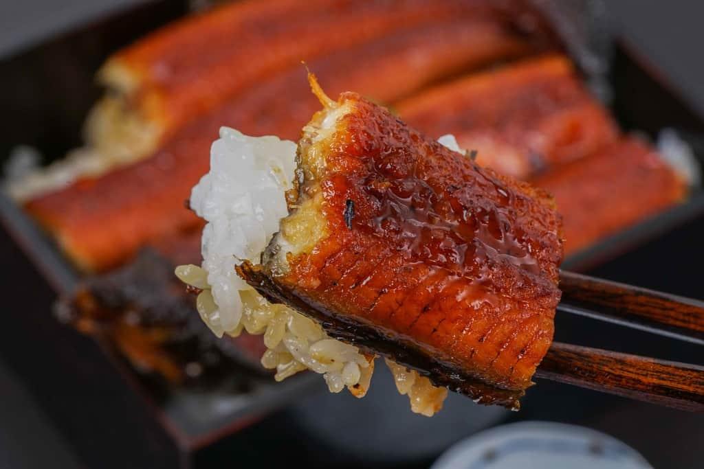 越前かに職人甲羅組の鹿児島県産特大うなぎ蒲焼きとご飯を箸でつまむ、うな重を箸でつまむ