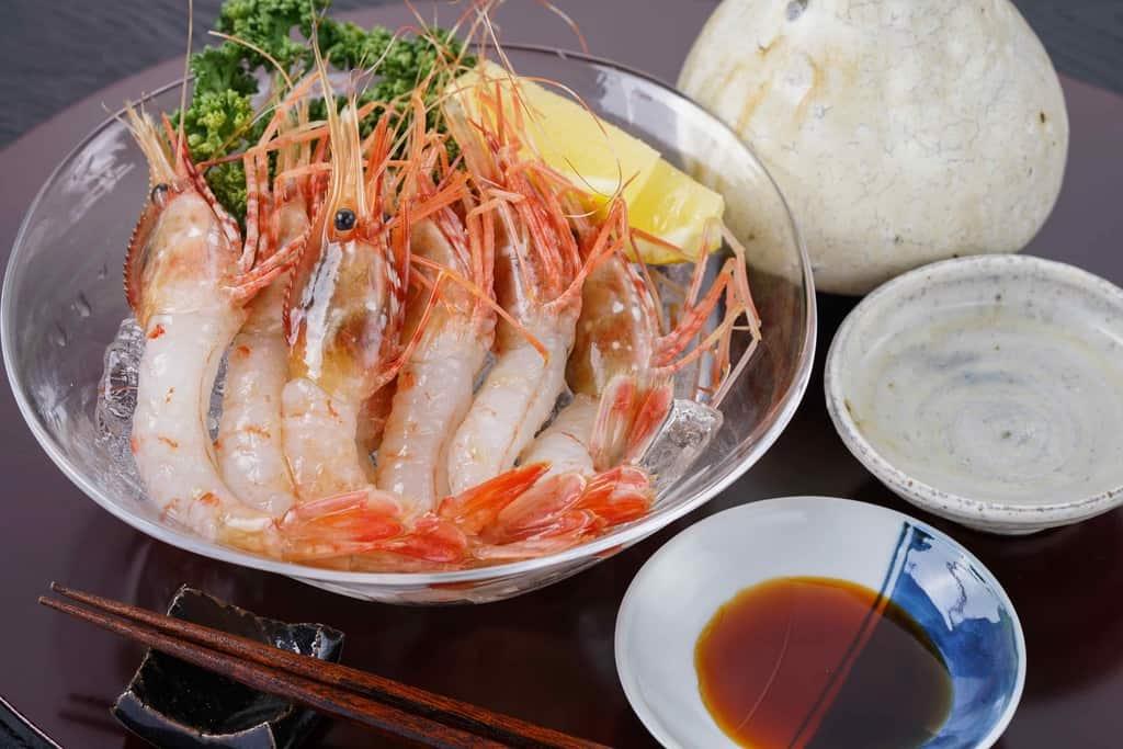 ガラスの器に盛られたぼたんえびの刺身・醤油・おちょこ・日本酒・箸・箸置き