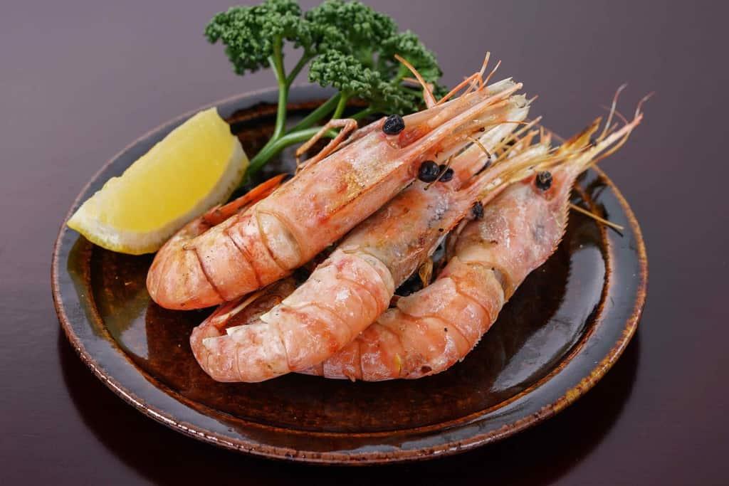 塩焼きした牡丹海老3尾とレモン・パセリを皿に盛り付ける、遠藤水産の朝獲れボタンエビの塩焼き