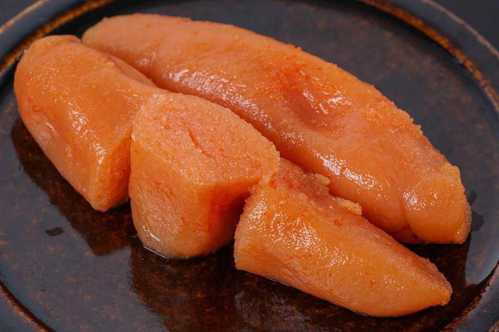飴色の皿の上の島本食品のオリジナル辛子明太子2本、カットして断面が見える状態の博多辛子明太子