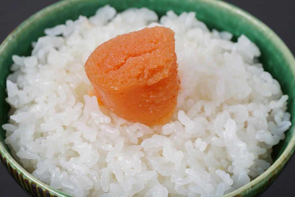 茶碗一杯の炊きたてご飯の上に島本のオリジナル辛子明太子ひと切れを乗せる、白飯の上の博多辛子明太子