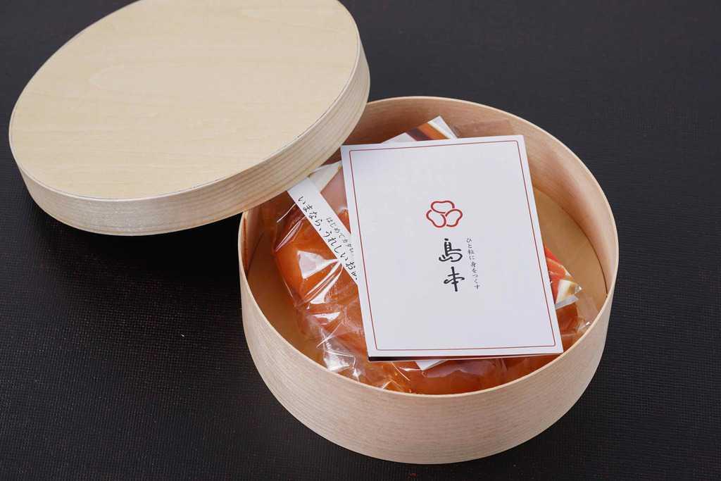 わっぱ型の折箱に入った島本食品のオリジナル辛子明太子240g、島本食品のオリジナル辛子明太子240gが入った容器のふたを開ける