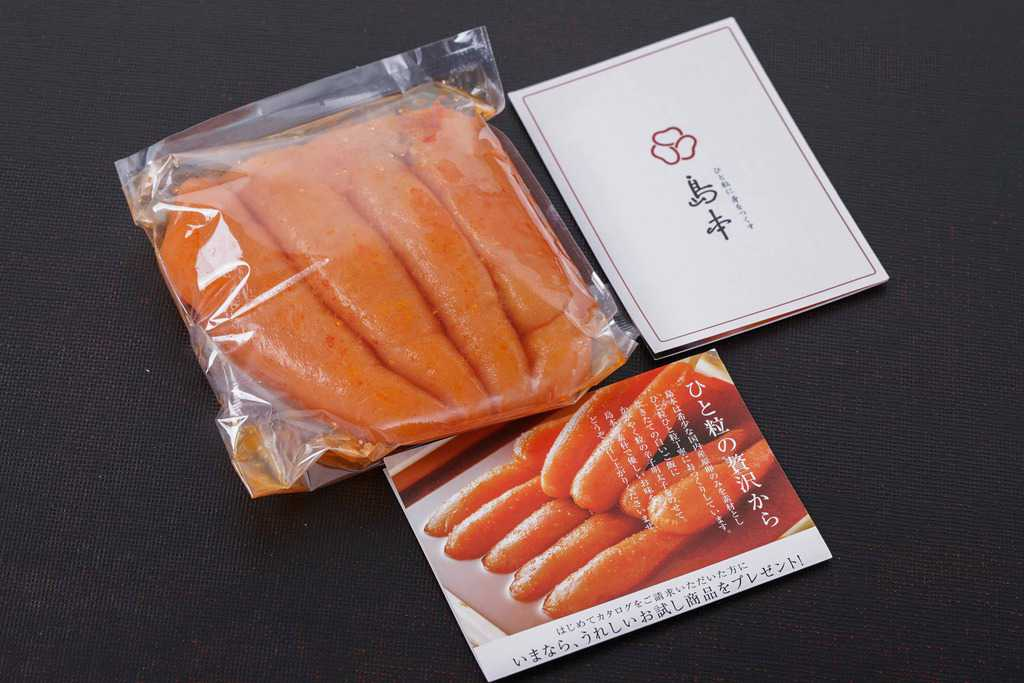 透明ビニール袋に入った島本食品のオリジナル辛子明太子240gとリーフレット
