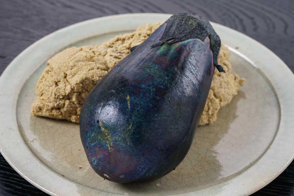 白い皿に盛り付けた泉州旬菜あかしやの水なすぬか漬け1個とぬか床のかたまり