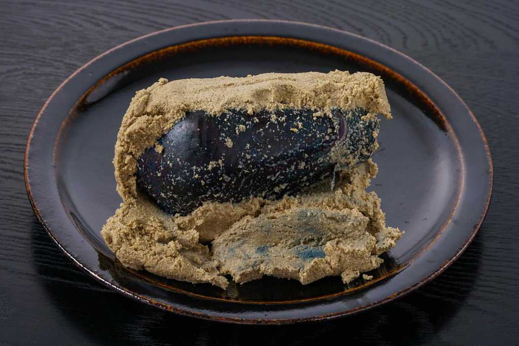 皿の上に盛られた泉州旬菜あかしやの水なす糠漬1個、糠を落としてナスが見える状態になった水茄子の糠漬け