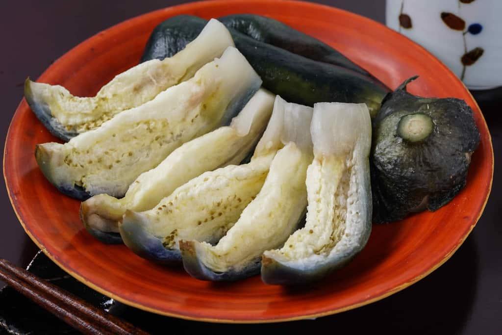 しっかりと漬かった泉州水なすの糠漬け・箸・湯のみ、泉州旬菜あかしやの水なす糠漬(水ナス漬)を切り分けて皿に盛り付け