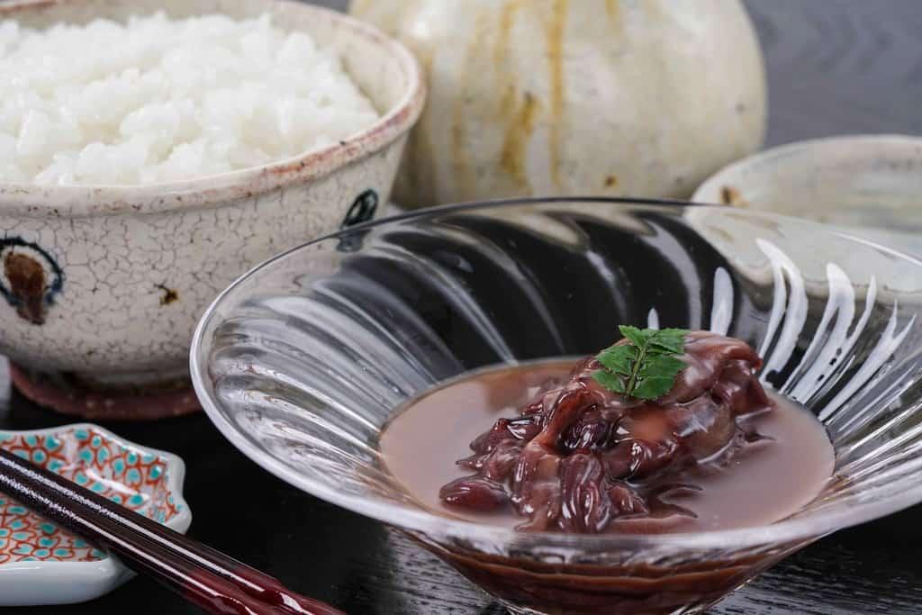 ガラスの器に盛り付けたホタルイカの沖漬け・茶碗一杯の白いご飯・日本酒・お猪口・箸・箸置き