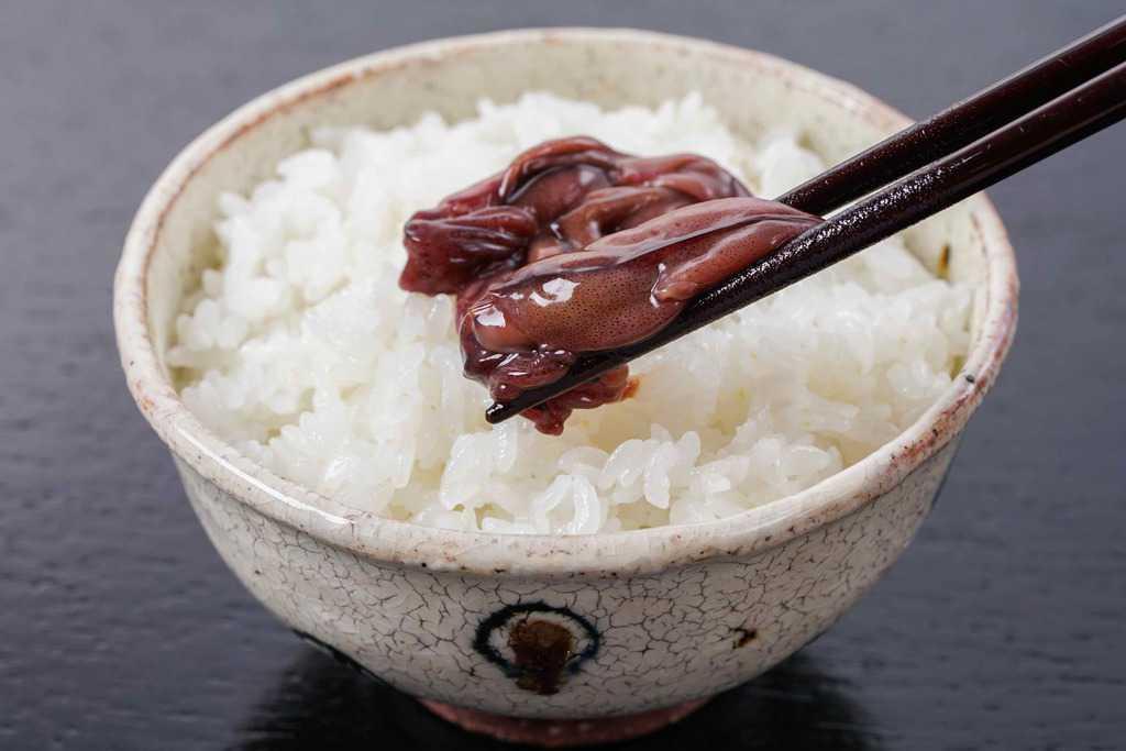 茶碗一杯の炊きたてご飯の上に箸でつまんだホタルイカの沖漬けを乗せる、ホタルイカの沖漬けご飯、富山名物ほたるいかの沖漬けをご飯に乗せる