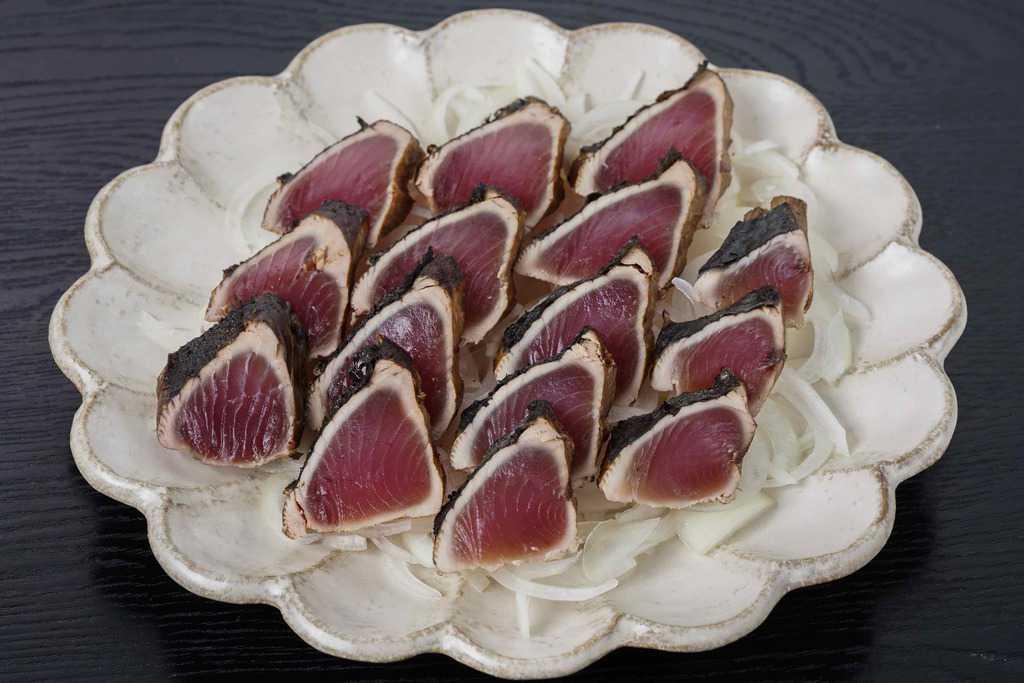 皿に盛り付けたオニオンスライスとカツオのタタキ、玉ねぎ薄切りの上に並べたカツオのたたき
