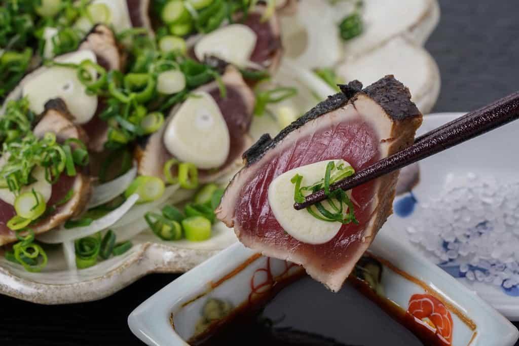 箸でつまんだかつおのたたきをタレにつける、高知県たたきやからおお取り寄せしたカツオのたたき