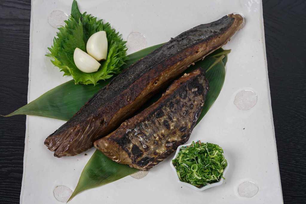 高知県たたきやから通販したカツオのたたき2節と青ネギ・にんにく・大葉を皿に盛り付ける、皿の上の鰹のタタキ