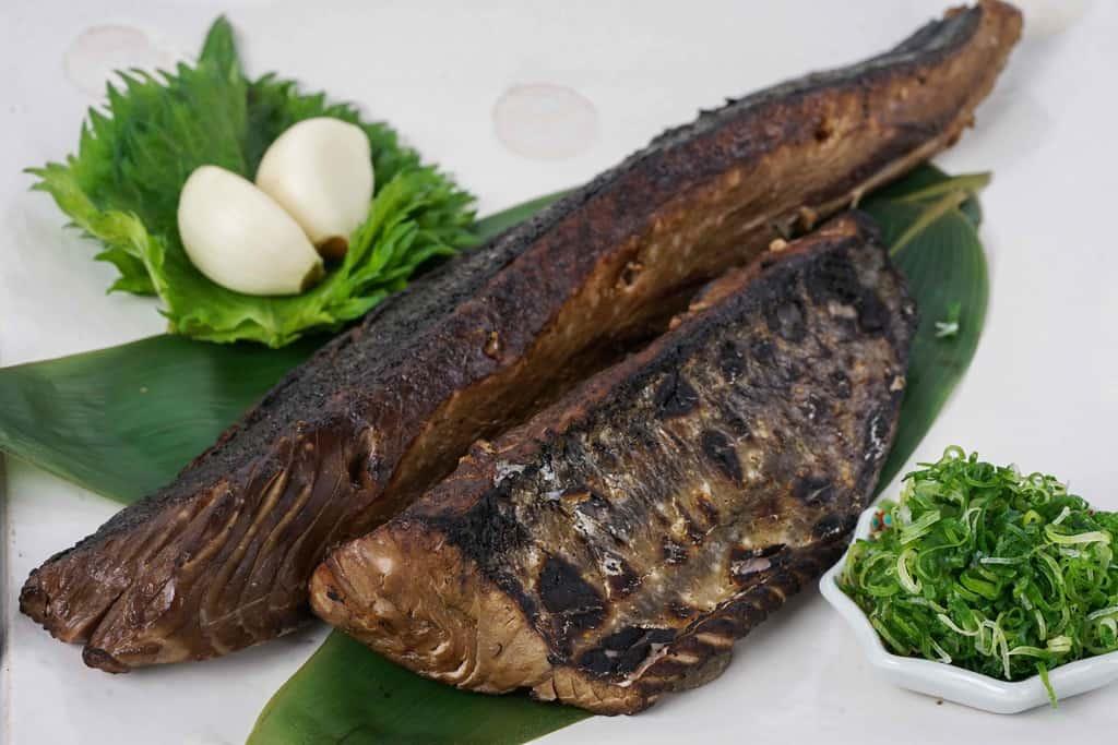 白い角皿の上の鰹のタタキ2節・青ネギ・にんにく・大葉、土佐料理たたき亭のかつおのタタキ