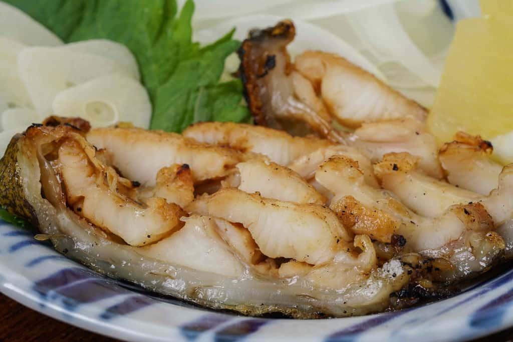 皿に盛り付けたうつぼのタタキ、ウツボのたたき・レモン・スライスニンニク・大葉・スライスオニオン