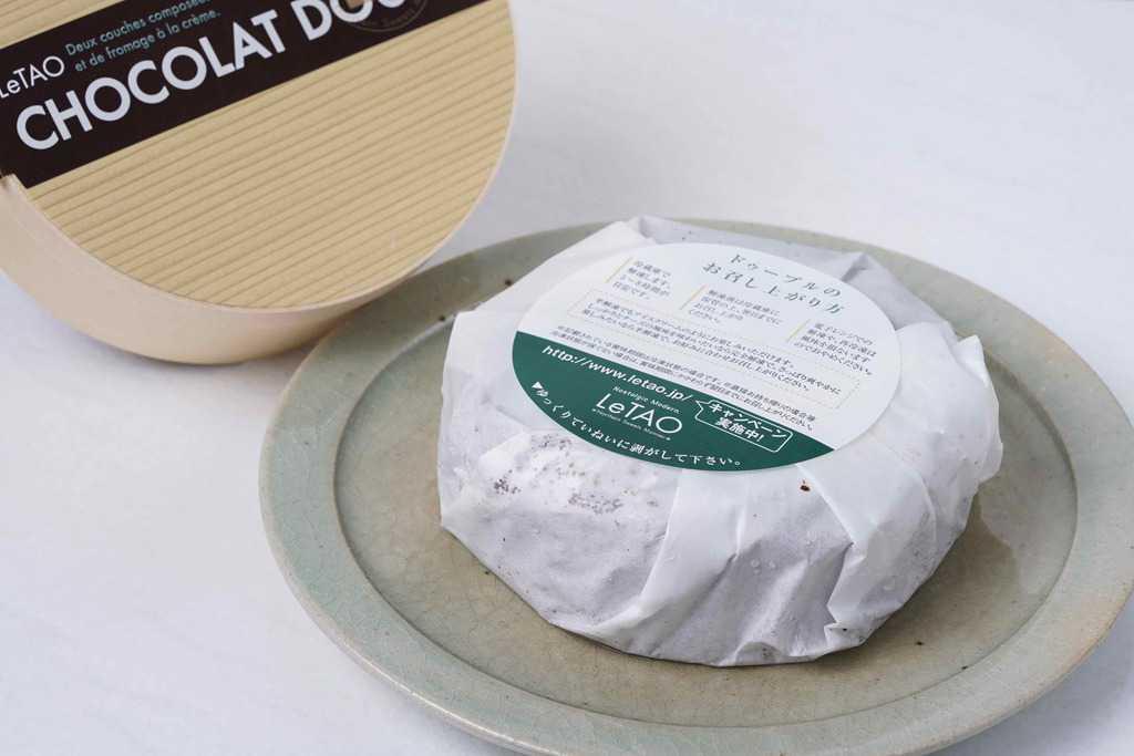 箱から取り出した小樽洋菓子舗ルタオのショコラドゥーブル4号、包装紙に包まれたショコラドゥーブルを皿に乗せる