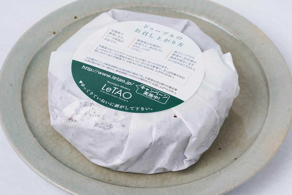 皿の上にある包装紙に包まれたルタオのショコラドゥーブル4号