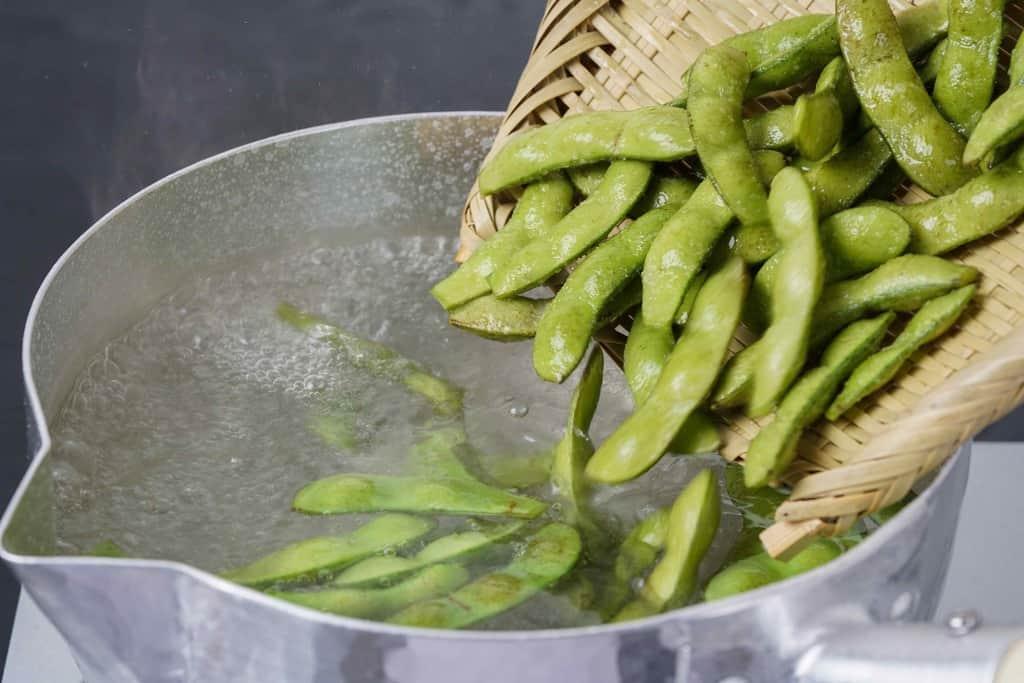雪平鍋の中の沸騰したお湯に生の枝豆「おつな姫」を投入する、熱湯でゆでる枝豆