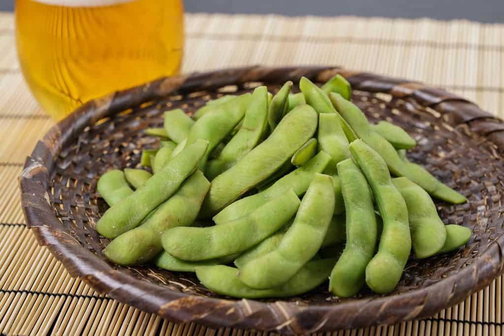 竹ざるの上に盛られた塩茹で枝豆、ゆでた枝豆「おつな姫」とビール