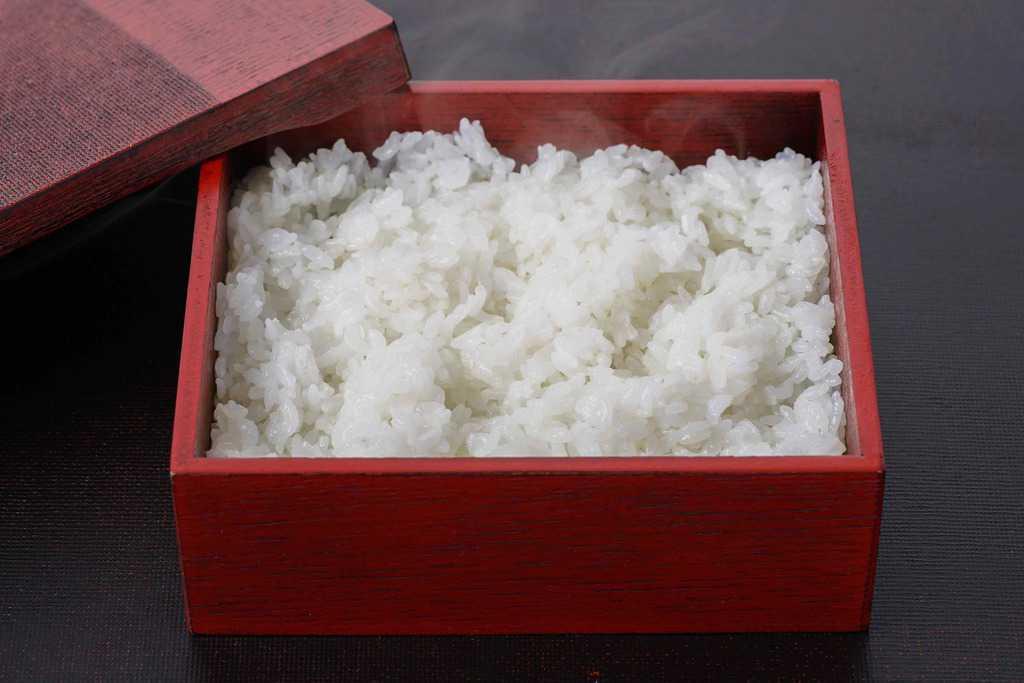 うな重用の角弁当箱に炊きたてのご飯をつめる、重箱に入った白飯