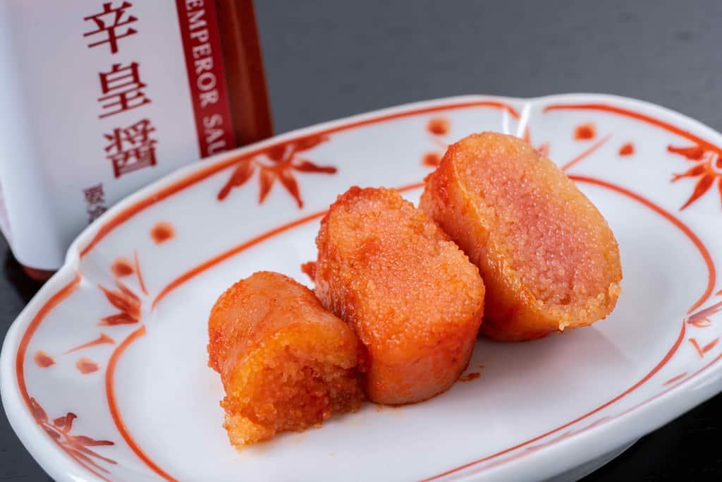 皿に乗ったふくやの激辛明太子3切れと辛皇醬(ホットエンペラーソース)