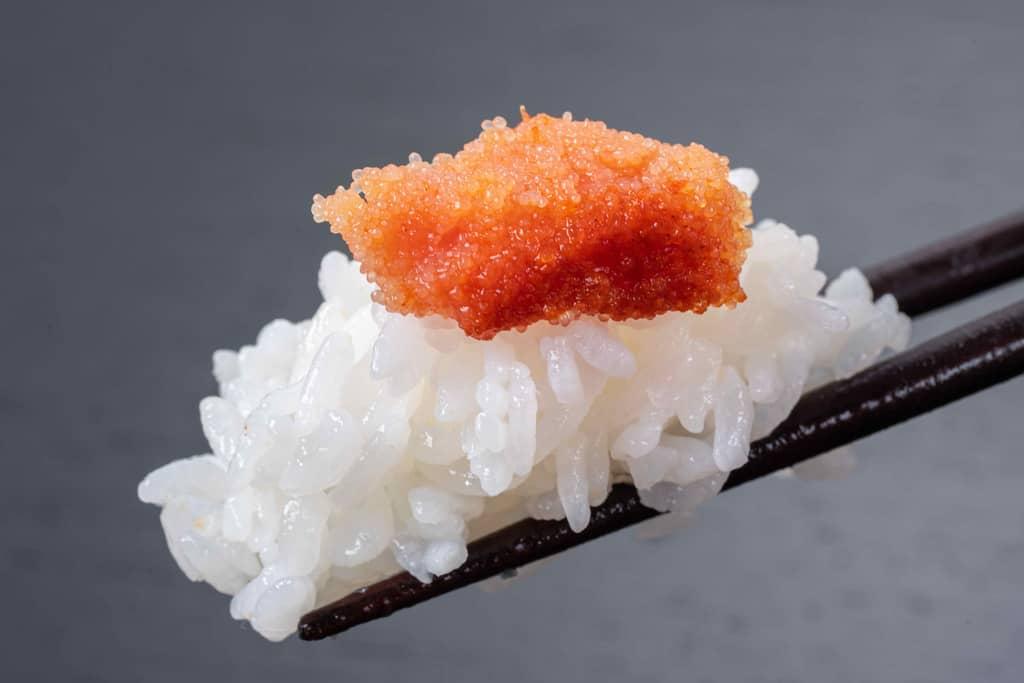 箸でつまんだご飯とその上の博多ふくやの辛子明太子「辛皇(ホットエンペラー)」、明太子ご飯