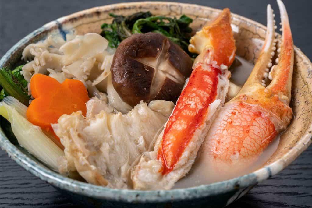 とんすいに取り分けたずわい蟹鍋の具材、野菜・ズワイガニの足肉・爪肉・肩肉・しいたけ・にんじん・長ねぎ・春菊・舞茸