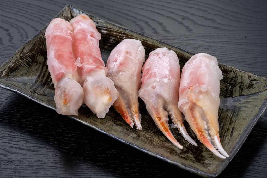 皿の上に並べた冷凍ズワイ蟹の爪肉