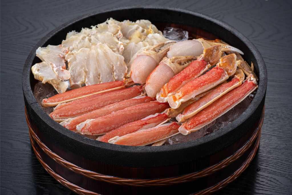 桶に山盛りの生ズワイ蟹、越前かに職人甲羅組のカット生ずわい蟹