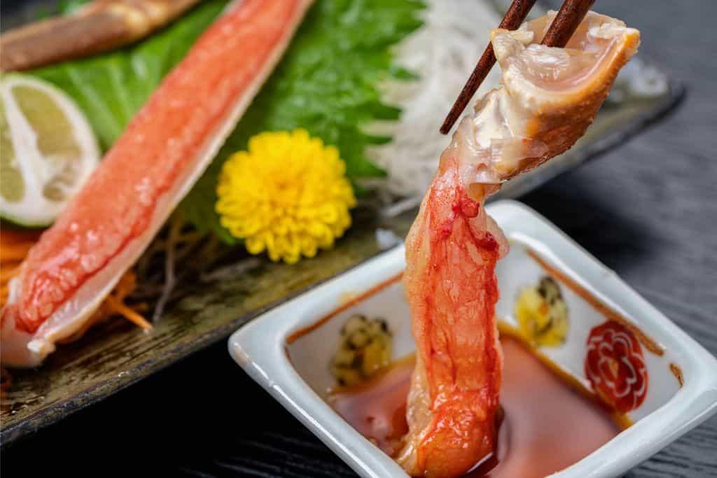 生ズワイガニの刺身を醤油につける、蟹の刺身