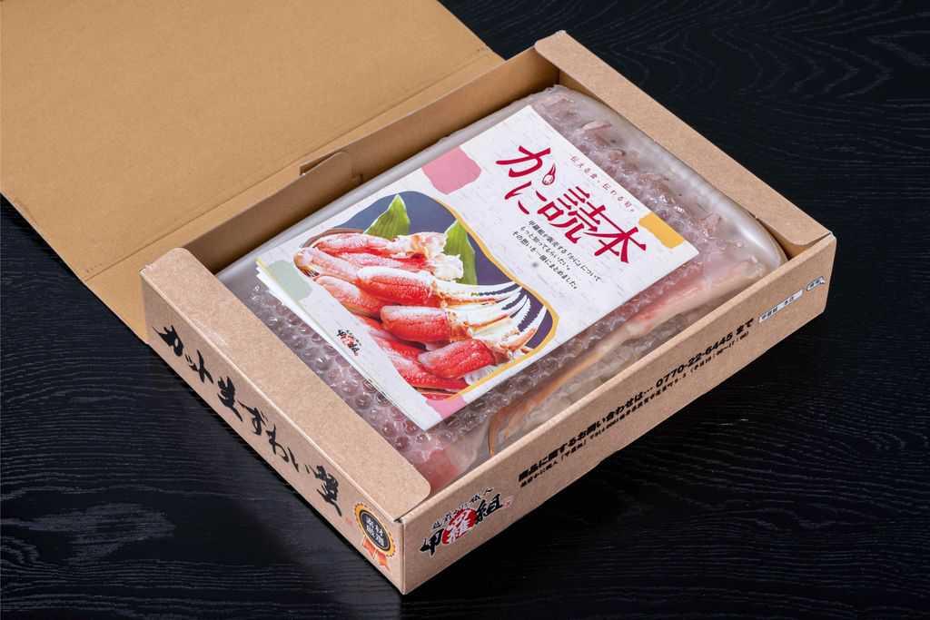 箱に入った越前かに職人甲羅組のカット生ずわい蟹700gとリーフレット、通販・お取り寄せズワイ蟹
