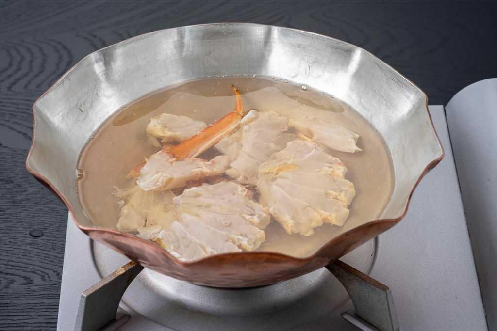 銅鍋で作る蟹鍋、スープの入った銅鍋にズワイガニの肩肉を入れる