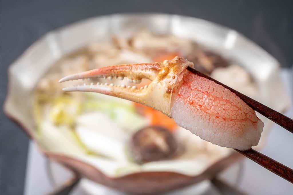 生ズワイガニの爪肉を箸でつまんで蟹鍋に入れる
