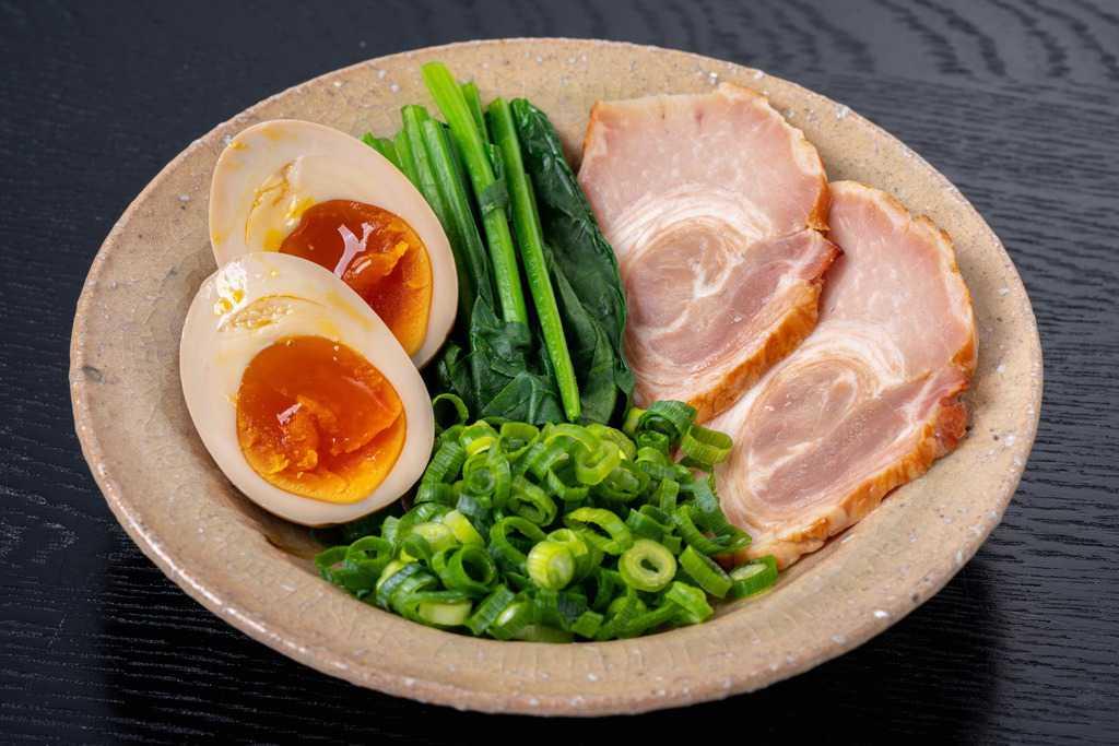 小鉢に盛られたチャーシュー・茹でたほうれん草・煮卵・ネギ、ラーメンの具材